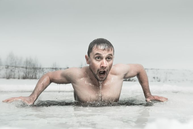 56243205 - man swimming in the ice hole with emotional face